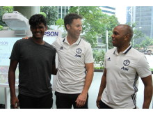 (From left to right) ActiveSG Football Academy Assistant Coach and SportCares youth Pravin Raj gleaning football tips from Manchester United legends Ronny Johnsen and Quinton Fortune.