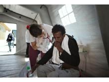 En sjuksköterska från Läkare Utan Gränser undersöker en man från Eritrea som har anlänt i Italien.