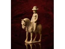 Kvinna med ridhatt till häst