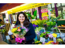Blooming beautiful: a shopper picking up some flowers in Rochdale market
