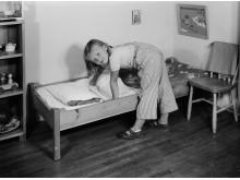 Bäddar egen säng, 1950-tal. Foto Ateljé Wahlberg, Nordiska museet.