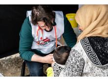 Läkare Utna Gränsers läkare Stefanos Tsallas vaccinerar ett barn på ett flyktingläger i Grekland