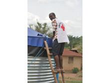 Volontär från Liberias Röda Kors hjälper till med vattenanläggning