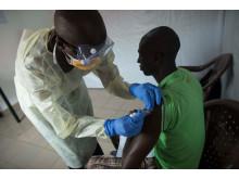 En patient som deltar i den kliniska studien i Guinea får en dos ebolavaccin.