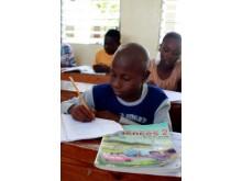 Elev i nyöppnad skola i Haiti