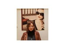 Karin Winroth isttande vid affisch roterad