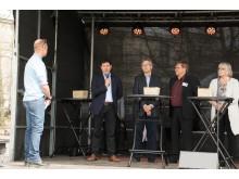 Peter Olofsson, landstingsråd (S) och Björn Jonsson, ordförande för föreningen Hjältarnas hus i samspråk på scenen.