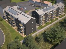 Översiktsillustration av de nya husen i kvarteret BoKlok Staben, Karlskrona. På taken syns solceller som skapar energi till fastighetsel.