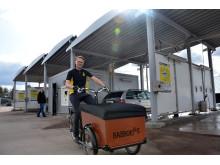 Anders Nygårds på elassisterad lådcykel framför tvättstationen i Falun