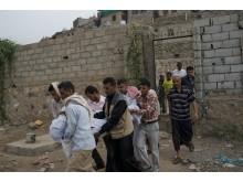 En kvinna bärs till begravningaplatsen i Taiz, Jemen. Hennes hus har träffats i en bombattack (bild tagen i juli 2015).