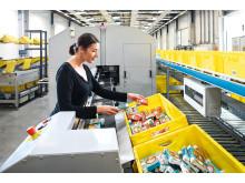 Produkterne hentes enkeltvist fra batch-beholderen og lægges på et transportbånd, som kører direkte ind i Schäfer-scanningsmaskinen