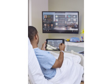 A patient uses a HP Pro Slate 10 EE Healthcare to control the tv monitor from his hospital bed. HP20150513500