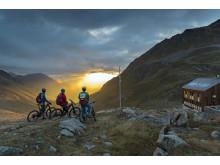 Mountainbiker genießen den Sonnenuntergang vor der Kesch Huette
