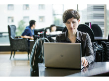 Woman using the HP EliteBook Folio 9470m at a table