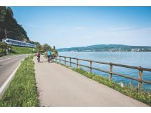 Tourenbiker Paar unterwegs am Bodensee bei Berlingen. Im Hintergrund der Thurbo Zug