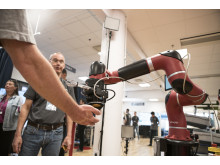 A collaborative robot passes candy to visitors