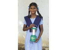 Jayamma visar upp familjens solcellslampa