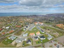 Montage med illustration av området med kvarteret BoKlok Smaragden i mitten, Färjestaden.
