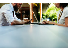 Mann og kvinne som bruker laptop og mobil paa cafe