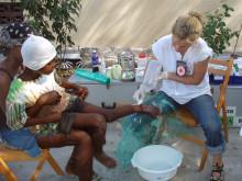 Röda Kors-delegat i Haiti tvättar ett sår på en flickas ben