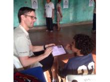 Tomas Hjalmarsson hjälper en pojke att se bättre under Optiker utan gränser 2016
