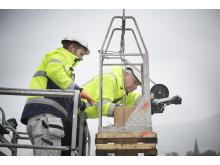 Murmester Thomas Djønne og Sturle Stenhjem, Leca-representant i Bergen firer ned et keramisk innerrør