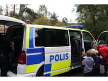 Nyfikna besökare kikar in i polisbilen
