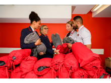Virgin Trains employees with blankets and street bags made out of old uniforms