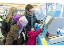 Familie sjekker inn ved Oslo Lufthavn
