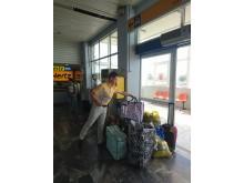 En af Spies' guider, Sebastian Diggins, samler gæsternes hjælpepakker i lufthavnen på Lesbos, inden de bliver hentet af frivillige fra den lokale kirke.