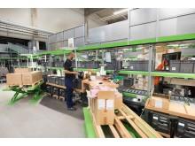 På sakselifte til paller kan medarbejdere ompakke varer ergonomisk i forsendelseskasser til shuttle-systemet.