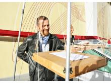 Kunstner Lars Kristian Gylver viser frem pendelen som har blitt brukt til å lage deler av kunsten.