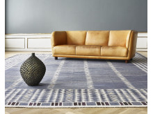 "Arne Jacobsen's unique ""Novo"" sofa, Axel Salto's large stoneware vase and a carpet woven by Barbro Nilsson."