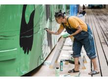 Konstnären Nathalie Ruejas målar en spårvagn i grönt.