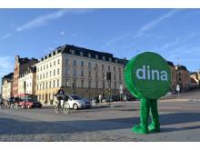 Dina Försäkringars maskot framför Dina Försäkringars fastighet på Skeppsbron i Stockholm