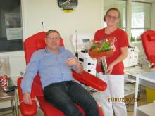 Hans Henrik Samson Olsen, 100 gangs donor, får overrakt blomster af Dorte Pedersen.