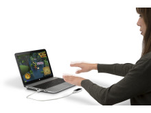 HP ENVY 15 TouchSmart PC with Leap Motion Controller, Right Facing. Woman interacting with Leap Motion controller and JungleJumper Game.