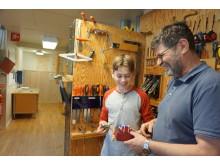 Läraren Kenneth Remnås tittar på den båtbil 14-åriga Adam Benjaminsson har tillverkat efter ett av förskolebarnens ritningar.