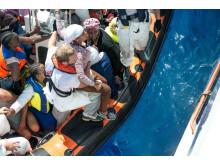 Akutsamordnaren Will Turner från Läkare Utan Gränser hjälper en kvinna under en räddningsinstats.