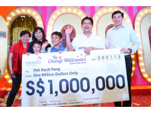 Mr Peh and his family receiving the S$1 million cheque from Mr Lee Seow Hiang, CEO of Changi Airport Group