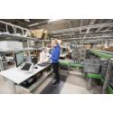 Verkkokaupan työasemissa yhdistellään riippuvat tavarat ja hyllytavarat, jotka pakataan kuljetuslaatikoihin.