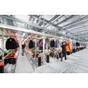 Työntekijät käyttävät radiotaajuisia päätteitä riippuvien vaatteiden poimintaan.
