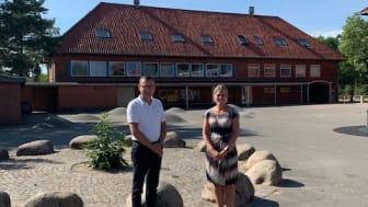 Formand for Børne- og Skoleudvalget Daniel E. Hansen (V) og skoleleder Annika Palmelund foran én af de to skolegårde, der skal renoveres.