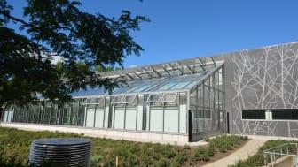 Den nya byggnaden i betong med inslag av grafiskt mönster i fasaden och ett stort växthus i glas ger forskningsanläggningen en egen karaktär i samklang med befintliga byggnader i trä och tegel. Foto: Petra Stenberg