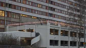 Bokstäverna i Alexandra Stratimirovics ljusgestaltning ligger som en ljuskrona över garagebyggnaden. Vid en närmare titt bildar bokstäverna ord och meningar.