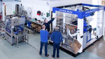 Air Grip World från Yaskawa låter roboten resa upp lådor och packa ner flaskor.