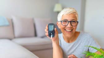 Ältere lachende Frau mit Blutzuckermessgerät