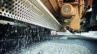 ClAir Asphalt: Das mit Titandioxid versetzte Granulat wird über den fertigerintegrierten Streuer in die Asphaltdeckschicht eingebunden. copyright: STRABAG AG