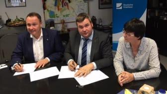 Bürgermeister Enrico Schilling (Mitte) und Michael Kölling, Regional Manager Mitteldeutschland Süd Deutsche Glasfaser unterzeichnen im Beisein der Ortsbürgermeisterin Gräfenhainichens Christel Lück (rechts) den Kooperationsvertrag