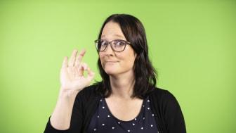 """Maria Norberg, konsult på Teckenbro, medverkar i seminariet """"Hög tid för teckenspråkiga böcker!"""" på Bokmässan 2021. På fotot gör hon tecknet perfekt mot en grön bakgrund. Foto: Mikael Sundberg/MTM."""